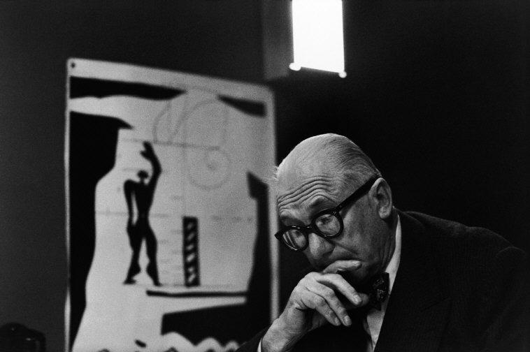 "FRANCE. Ile-de-France region. Paris. 1959. 7th arrondissement. 35, rue de Sèvres. The painter, architect and city planner LE CORBUSIER in the ""Atelier 35 S"". On the left: a lithograph of his ""Modulor""."